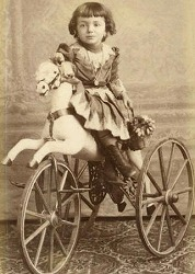Victorian horse trike with wooden wheels & spokes, no metal tread though.